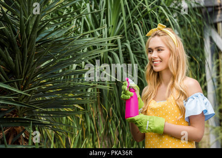 attractive smiling blonde woman holding sprayer and watering green plants - Stock Photo