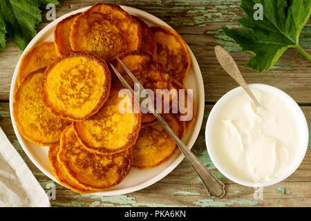 Homemade pumpkin pancakes with sour cream, ripe pumpkin and pumpkin leaves. Selective focus. - Stock Photo