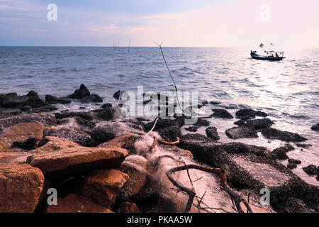 Rocky Beach during sunset with fisherman's boat in the background - Stock Photo