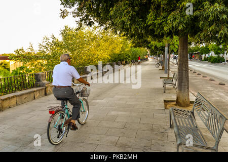 Cordoba/ Spain - 08/20/18 - A man biking along the river in the old town area of Cordoba - Spain - Stock Photo