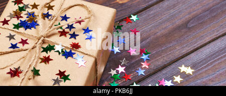 Gift box with star. Creative concept with festive decor on black background. Confetti stars, red, yellow with gift box. Explosion of confetti. - Stock Photo