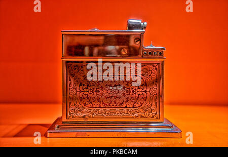 Old Used vintage Silver metal lighter red background smoker zippo light open burn one used tobacco macro equipment wheel object gas gasoline shiny met - Stock Photo