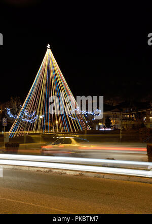 Christmas tree in park in Kastoria , Greece and light trails of car - Stock Photo