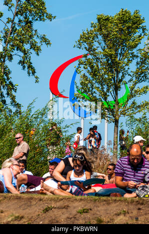 People sitting in front of the Paralympic symbol at the London Olympic Park 2012, England, UK - Stock Photo