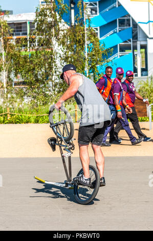 A BMX rider performing tricks with Olympic staff walking past at the London Olympic Park 2012, England, UK - Stock Photo