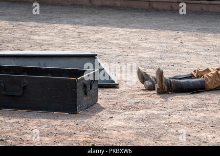 Coffin next to a dead man with his boots on a dirt road in a wild west city - Stock Photo
