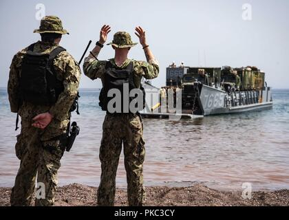 Djibouti. 8th Mar, 2018. DJIBOUTI (Sept. 8, 2018) Engineman Fireman Cory Durenberger, assigned to Beach Master Unit (BMU) 1, signals a landing craft utility while participating in Theater Amphibious Combat Rehearsal (TACR) 18. Led by Naval Amphibious Force, Task Force 51/5th Marine Expeditionary Brigade, TACR integrates U.S. Navy and Marine Corps assets to practice and rehearse a range of critical combat-related capabilities available to U.S. Central Command, both afloat and ashore, to promote stability and security in the region. U.S. 5th Fleet and coalition assets are participating in nume - Stock Photo