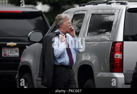 National Security Advisor John Bolton speaks on a phone on the South Lawn of the White House in Washington, DC, September 11, 2018. Credit: Olivier Douliery/Pool via CNP | usage worldwide - Stock Photo