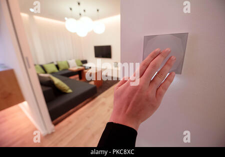 12 September 2018, Baden-Wuerttemberg, Waeschenbeuren: 12 September 2018, Germany, Waeschenbeuren: An employee of the smart home provider Loxone operates a switch on the wall in one of the company's showrooms, which can be used, among other things, to control the room lighting or the music system. Loxone settled in Wäschenbeuren east of Stuttgart some time ago and relies on self-contained complete systems that can control various electronic components in a building. (on dpa 'Das Haus denkt mit - Wie Smart Homes das Leben verändern sollen' from 13.09) Photo: Marijan Murat/dpa - Stock Photo