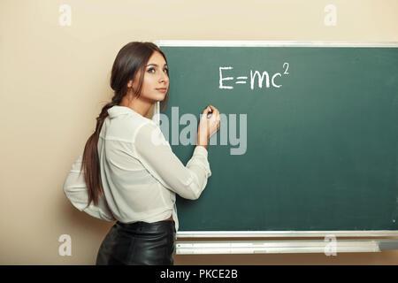 Beautiful young girl teacher writing formula on the blackboard. - Stock Photo