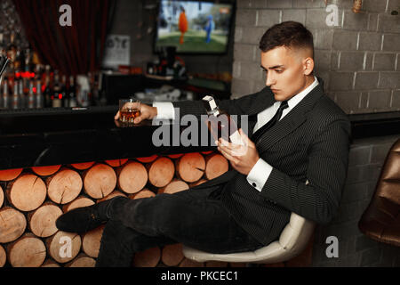 Handsome young man in a stylish suit holding a bottle of whiskey at the bar. - Stock Photo