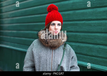 Stylish young Russian girl in fashionable winter clothes standing near a green wooden wall - Stock Photo