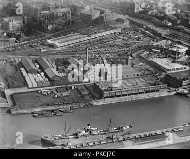 Floating Harbour, Canon's Marsh, Bristol, 1921. Aerial view showing a steamer docked in the floating harbour opposite a transit warehouse and railway goods yard. Tobacco warehouses were built here in the 1920s but these were blown up in 1988 and replaced by the Lloyds Bank building. In the background are St Augustine's Reach and Bristol Cathedral. - Stock Photo