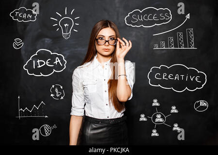 The young beautiful girl with glasses in a white blouse on the background of business icons and diagrams. The concept of a successful business woman - Stock Photo