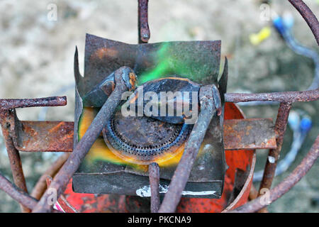 Aluminium gutter welding by using soldering copper with picnic gas:Preheat the soldering copper by frame from picnic gas. - Stock Photo