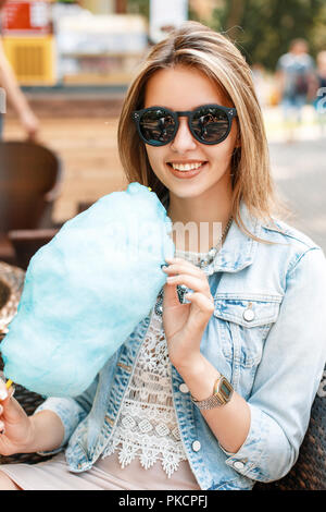 Pretty woman in sunglasses and a denim jacket eating cotton candy in the park. - Stock Photo
