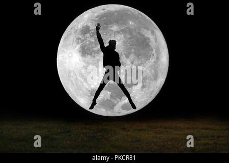 Image shadow ,Silhouette, of young cheerful jump all the way from the grass sticking out your right hand until all in fun page with the full moon. - Stock Photo