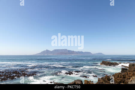 Cape Town, South Africa. View of Table Mountain on horizon, Photographed from Robben Island where Nelson Mandela was imprisoned. Rocks in foreground. - Stock Photo