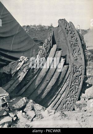 'The Oseberg ship in the mound, showing the carving on stem and railing', 1935. The Oseberg ship is a well-preserved Viking ship which was buried c834 AD, although the ship itself is thought to be older. It was discovered in a large burial mound at the Oseberg farm near Tønsberg in Norway. From A History of the Anglo-Saxons, Vol. II, by R. H. Hodgkin. [The Clarendon Press, Oxford, 1935] - Stock Photo