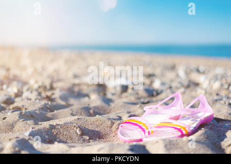 close-up of pair of sandals on empty beach on clear sunny summer day - Stock Photo