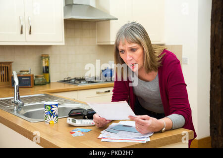 woman shocked by credit card bill / mortgage / loans - Stock Photo