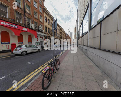 A bike chained to a street sign in Manchester City centre - Stock Photo
