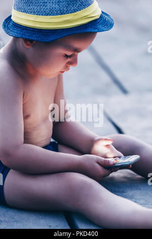 Cute little toddler boy with hat sitting on beach and playing with smartphone. Child learning how to use smartphone. Boy texting on the phone. - techn Stock Photo