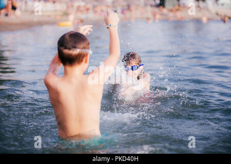 Happy children playing in the sea. Kids having fun outdoors. Summer vacation and healthy lifestyle concept - Stock Photo