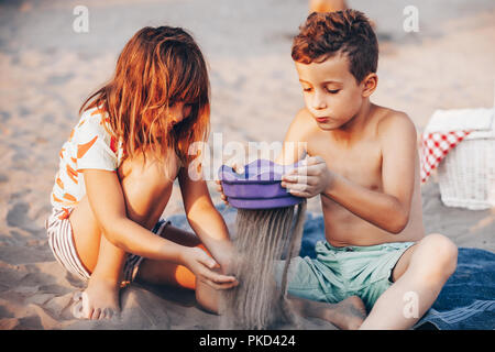 Happy positive children sitting on a towel on the beach and playing with sand. Summer vacation and healthy lifestyle concept - Stock Photo