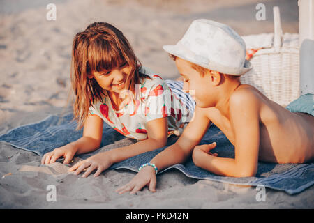 Happy positive children playing while lying on a towel on the beach.  Summer vacation and healthy lifestyle concept - Stock Photo