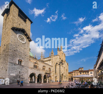 Piazza del Duomo in Como with view of the Lombard style architecture of Palazzo Broletto and the imposing facade of Como Cathedral - Stock Photo