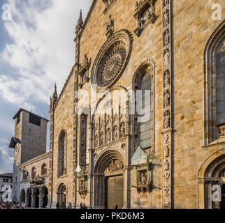 Piazza del Duomo in Como with view of the imposing facade of Como Cathedral and the Lombard style architecture of Palazzo Broletto - Stock Photo