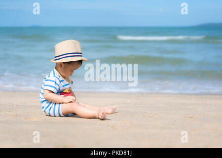 Portrait of a 10 months Asian baby boy with a hat sit in beach near sea in Phuket, Thailand. Summer, vacation, Travel and Holiday concept. - Stock Photo