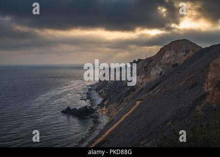 Stunning coastal view of sunset at the steep cliffs of Pelican Cove Park on a cloudy day with beams of sunlight poking through the clouds over Point V - Stock Photo