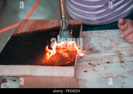 Burning wood planks in carpentry joint in Italy. Detail of gas burner and flames on black wooden texture. - Stock Photo