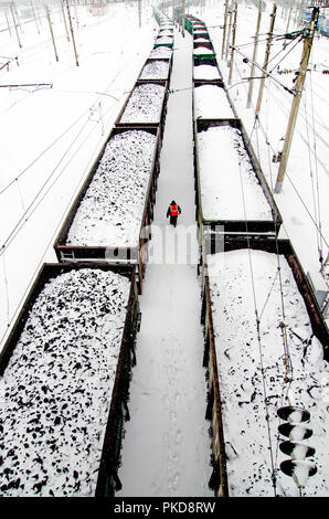 SIBERIA, RUSSIA - MARCH 20, 2018: Railway worker is walking between freight trains around Ekaterinburg, Russia. - Stock Photo