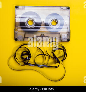 Old audio cassette with a tangled magnetic tape on a yellow background. Element of design. Vintage. - Stock Photo