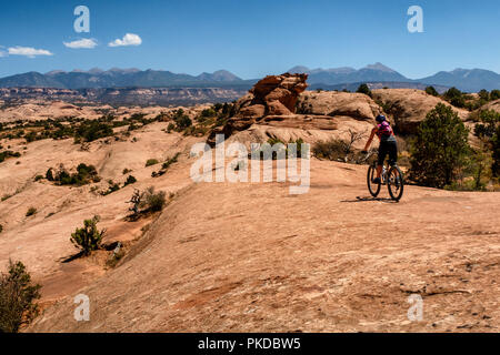 A woman rides a mountain bike on the world famous Slickrock trail in Moab, Utah, USA. - Stock Photo