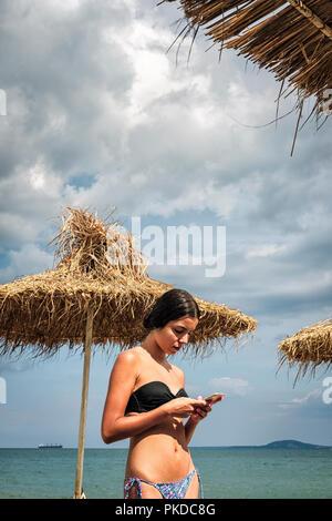 Teenage girl  in bikini looking at her phone on the beach - Stock Photo