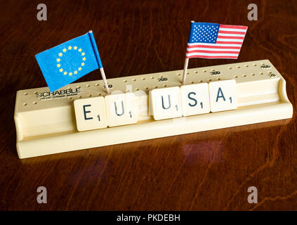 Scrabble letters spelling EU and USA with American and European Union flags on mahogany background to illustrate nation, trade and negotiation concept - Stock Photo