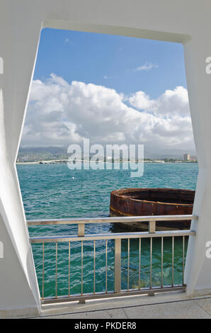 USS Arizona Memorial in Pearl Harbor, Hawaii, looking out from the monument to part of the USS Arizona rising from the water and Honolulu in the background. - Stock Photo