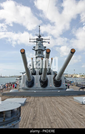 Tourists walk past gun turrets on USS Missouri (the ship on which the hostilities with Japan in WWII were officially ended) in Pearl Harbor, Hawaii. - Stock Photo
