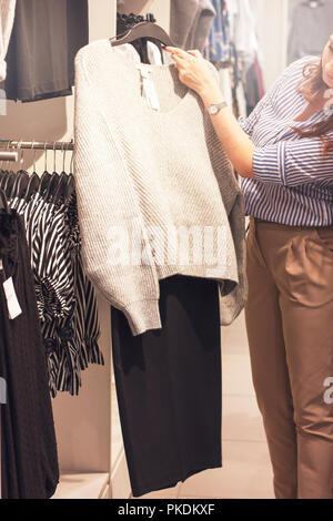 Young woman stylist shopper chooses clothes in the store - Stock Photo