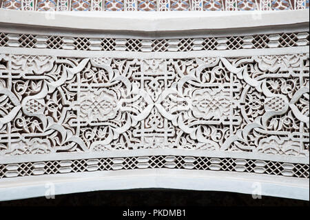 Moroccan intricate plaster work around doorway with traditional Moorish symbols and Arabic details, typical arches found in Marrakech, Morocco - Stock Photo