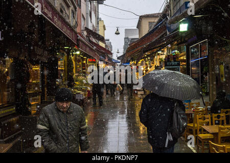 ISTANBUL, TURKEY - DECEMBER 30, 2015: Main street of Kadikoy market, on the Asian side of the city, with restaurants around, crowded, during a snow st - Stock Photo