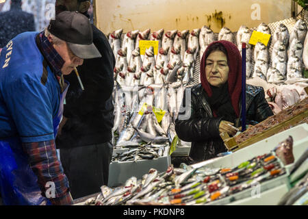 ISTANBUL, TURKEY - DECEMBER 30, 2015: Old woman wearing the islamic scarf buying fish in the fish market of Kadikoy, on the Asian side. Fish in the ma - Stock Photo