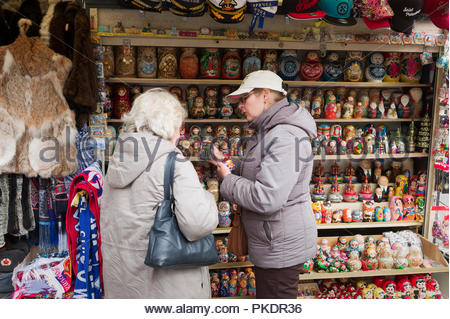 Female senior tourist buying a set of Russian nesting dolls from a street vendor in St.Petersburg, Russia - Stock Photo
