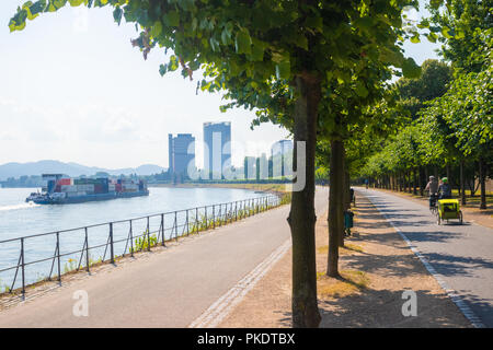 A view along the River Rhine Cycle and Footpaths with a cargo ship on the Rhine. - Stock Photo