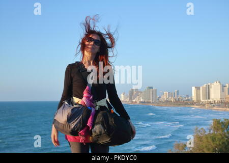 Young woman, traveler, tourist, dressed in black with pink scaref tied around bag with two hand bags stands relaxed, on hill, view at Tel Aviv bay. - Stock Photo