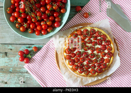 Tart, pie or cheesecake with cottage cheese and tomatoes and fresh tomatoes on a wooden background. Selective focus. - Stock Photo